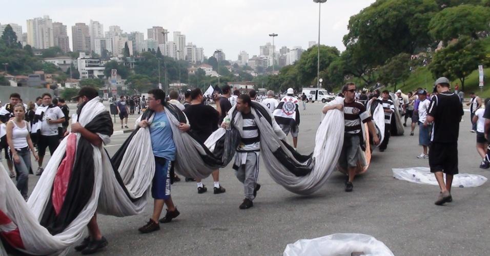 Torcida do Corinthians chega ao estádio do Pacaembu carregando uma bandeira para acompanhar a partida contra o Palmeiras