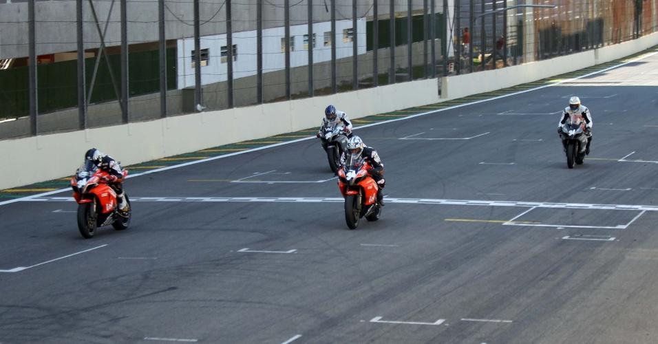 Cafu, de capacete branco, acelera sua moto preta e laranja na reta de Interlagos