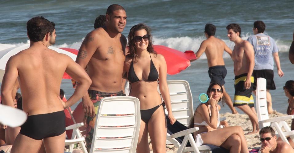 Adriano posa para foto ao lado de fã na praia do Rio de Janeiro, onde curte as férias com a família