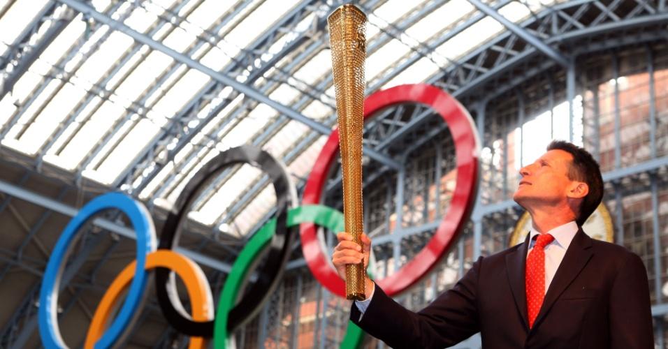 Sebastian Coe, chefe do Comitê Organizador da Olimpíada de 2012, posa com a tocha olímpica em londres (8/6/2011