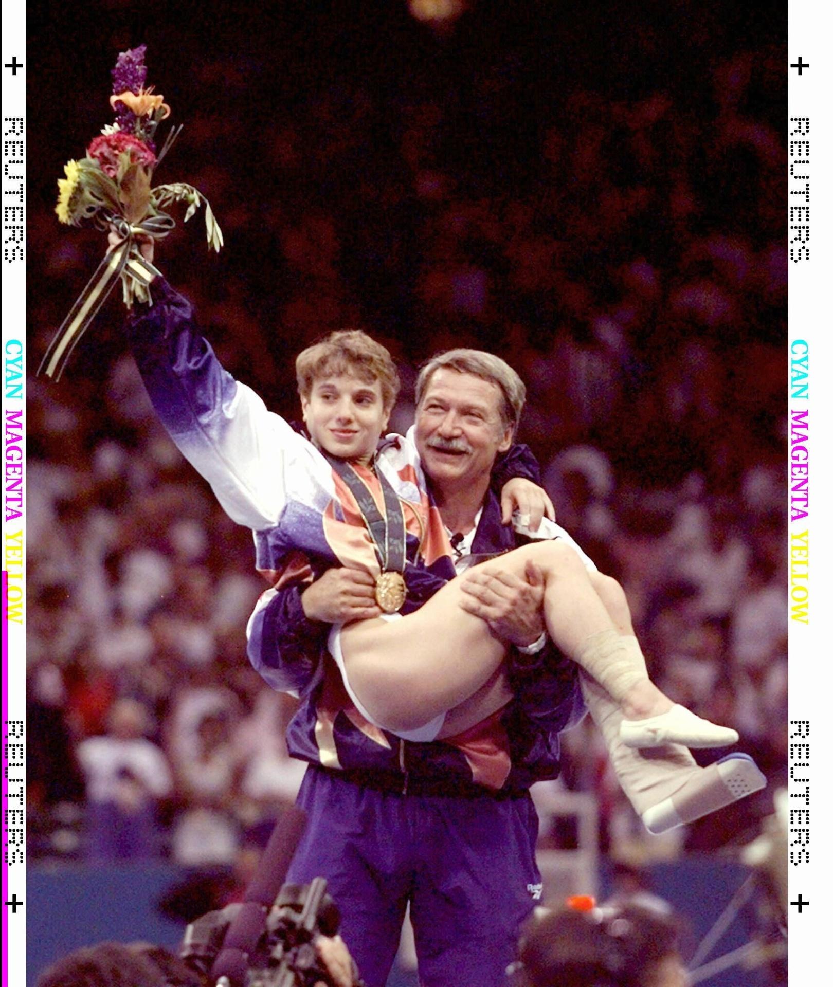 Heroína dos EUA ao saltar machucada, a ginasta Kerri Strug é carregada pelo técnico Bela Karoly