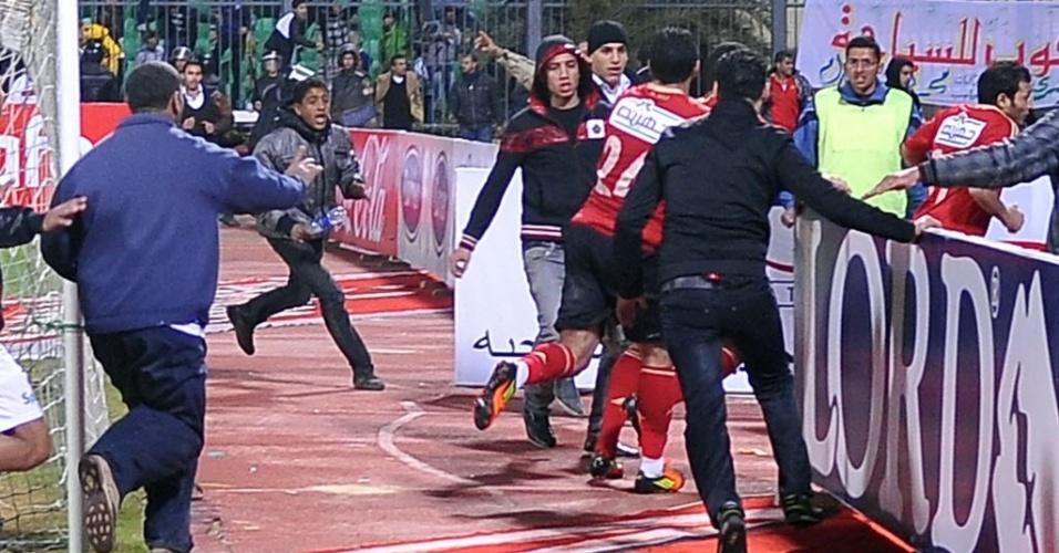 Jogadores do Al Ahly correm do gramado em meio à confusão após partida no Egito