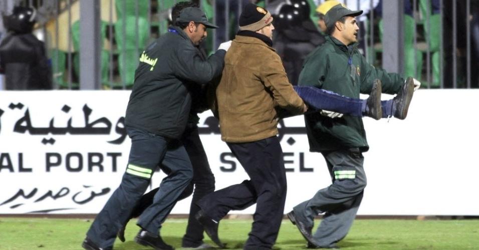 Médicos carregam corpo de torcedor ferido durante tragédia em estádio de futebol no Egito