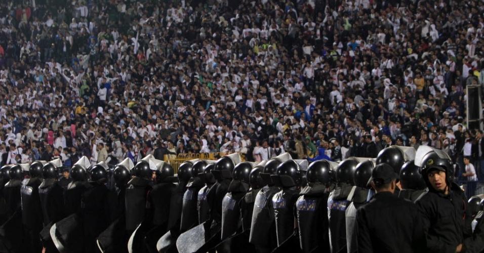Policiais fazem barreira contra a torcida após confusão em partida de futebol no Egito