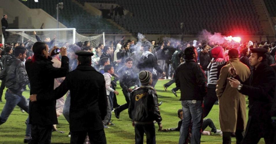 Policiais observam confusão entre torcedores após partida de futebol no Egito