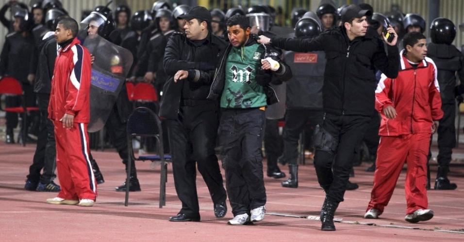 Policial socorre torcedor ferido após briga dos fãs do Al Ahly e do Al-Masry no Egito