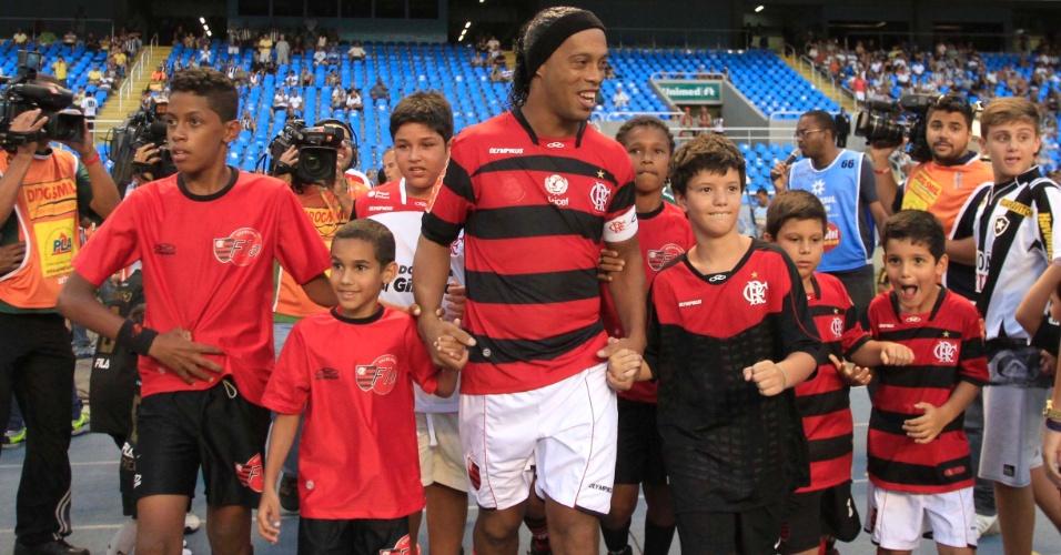 Cercado de jovens flamenguistas, Ronaldinho entra em campo para o clássico contra o Botafogo