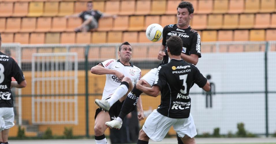 Leandro Castán (e), do Corinthians, tenta levar vantagem sobre dois jogadores do Bragantino no Pacaembu (05/02/2012)