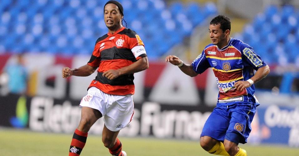 Ronaldinho Gaúcho conduz a bola marcado de perto por jogador do Madureira