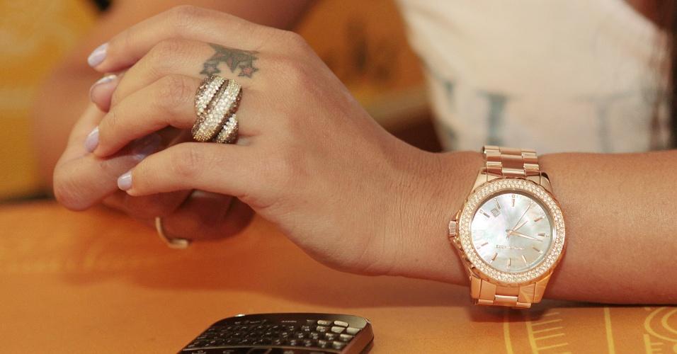 Detalhe da mão de Larissa Riquelme e seu conhecido celular, que ganhou notoriedade em 2010