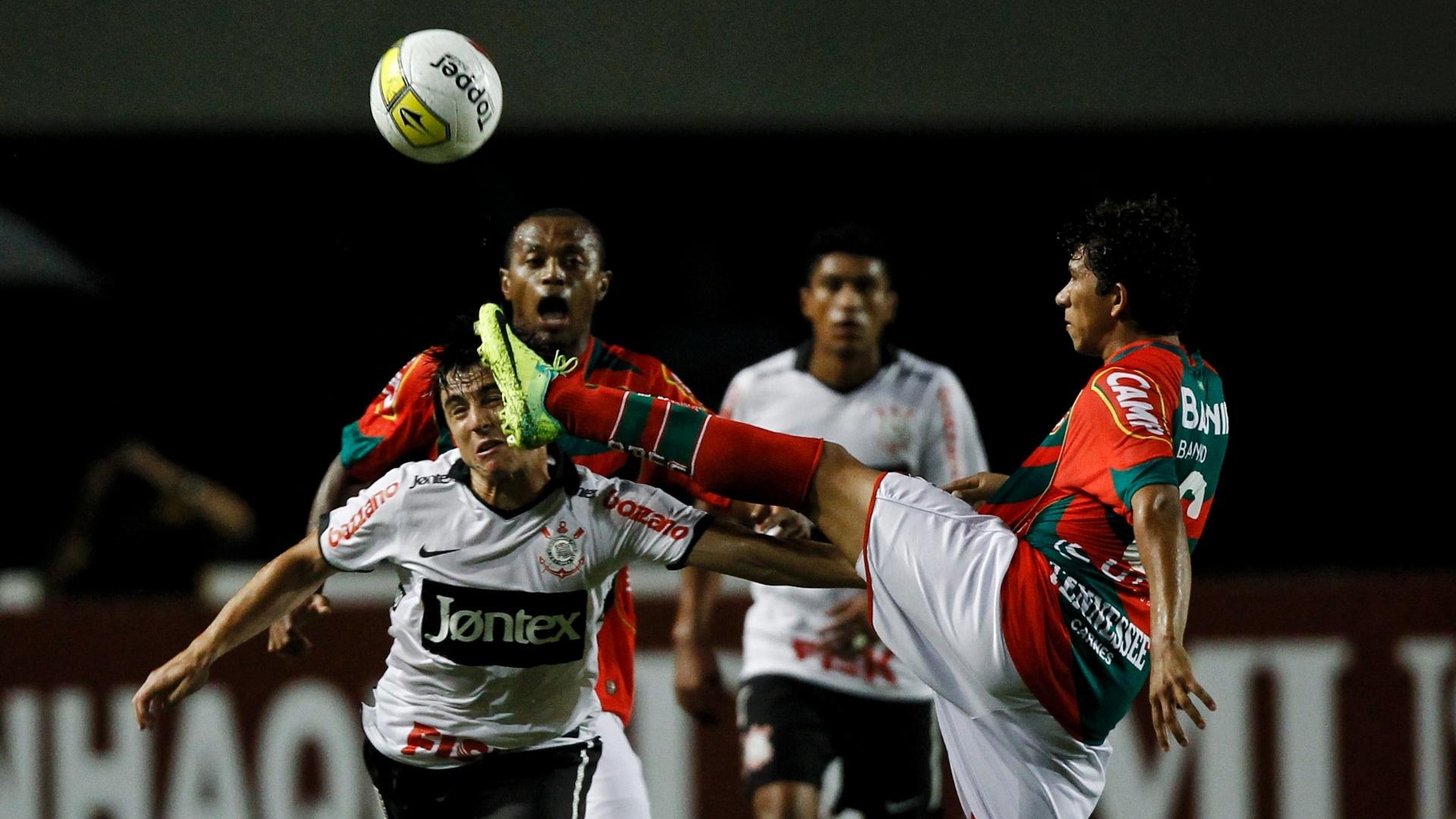 Jogador da Portuguesa ergue o pé na disputa de bola com Willian, atacante do Corinthians