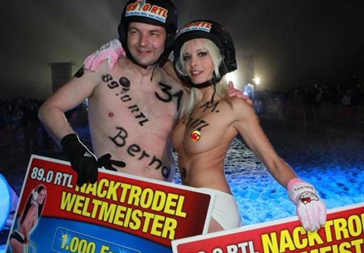 Campeã entre as mulheres, atriz pornô Mia Magma posa ao lado do vencedor Bernd Malyska com os prêmios do campeonato de trenó sem roupa de Braunlage, na Alemanha