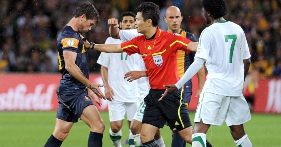 Árbitro coreano Kim Dong Jin separa Harry Kewell (esq.) e Kamil Saddiq Almousa durante partida entre Austrália e Arábia Saudita pelas Eliminatórias da Copa-2014