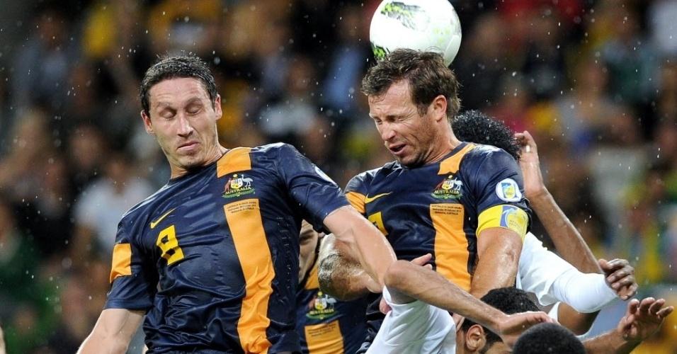 29.fev.2012 - Lucas Neil e Mark Mulligan, da Austrália, saltam sobre jogadores da Arábia Saudita na vitória por 4 a 2 pelas eliminatórias da Copa-2014