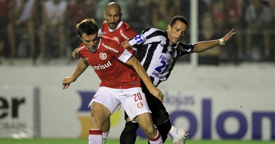Dagoberto (e) divide a bola observado por Guiñazu, em partida válida pela segunda rodada do Gauchão