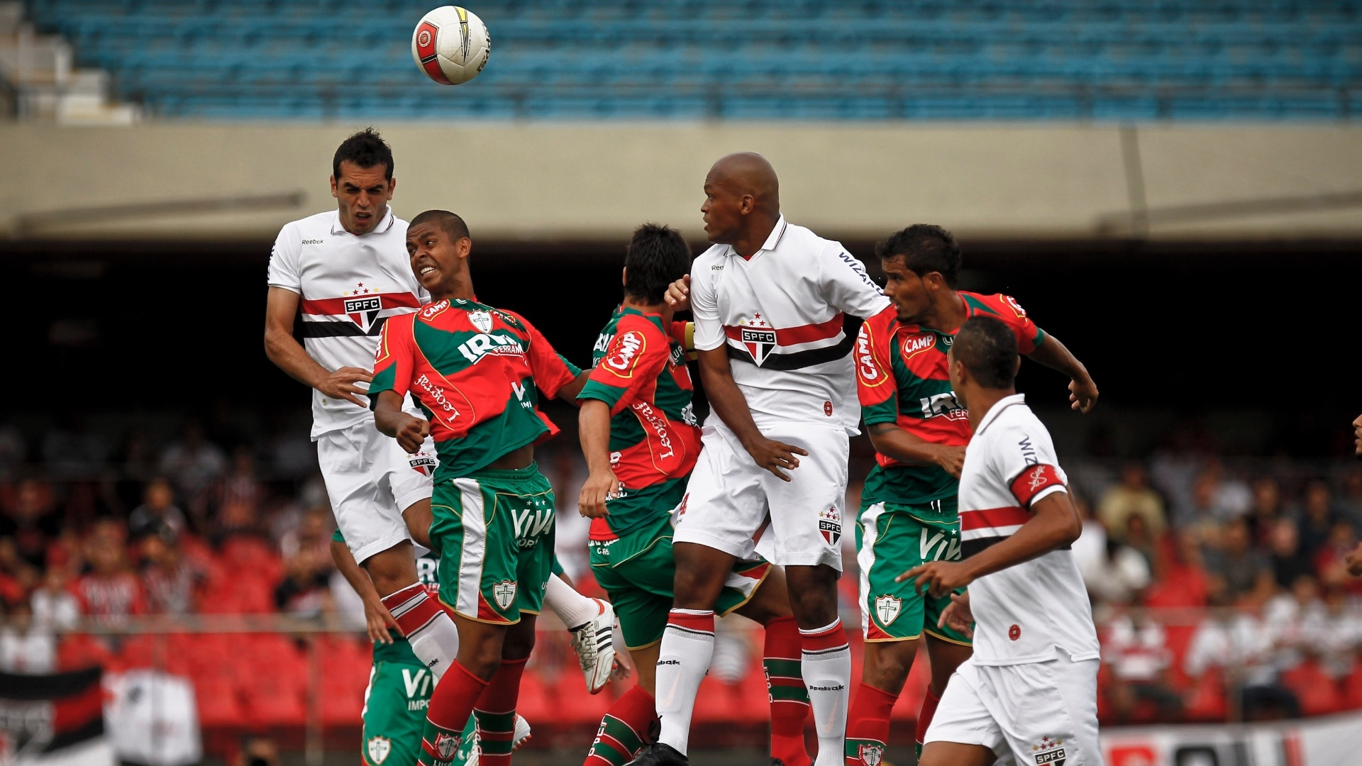 Jogadores do São Paulo e da Portuguesa brigam pela bola em jogada aérea
