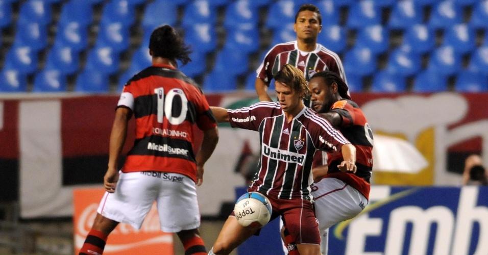 Ronaldinho e Vágner Love disputam a bola com Diguinho (c), do Fluminense