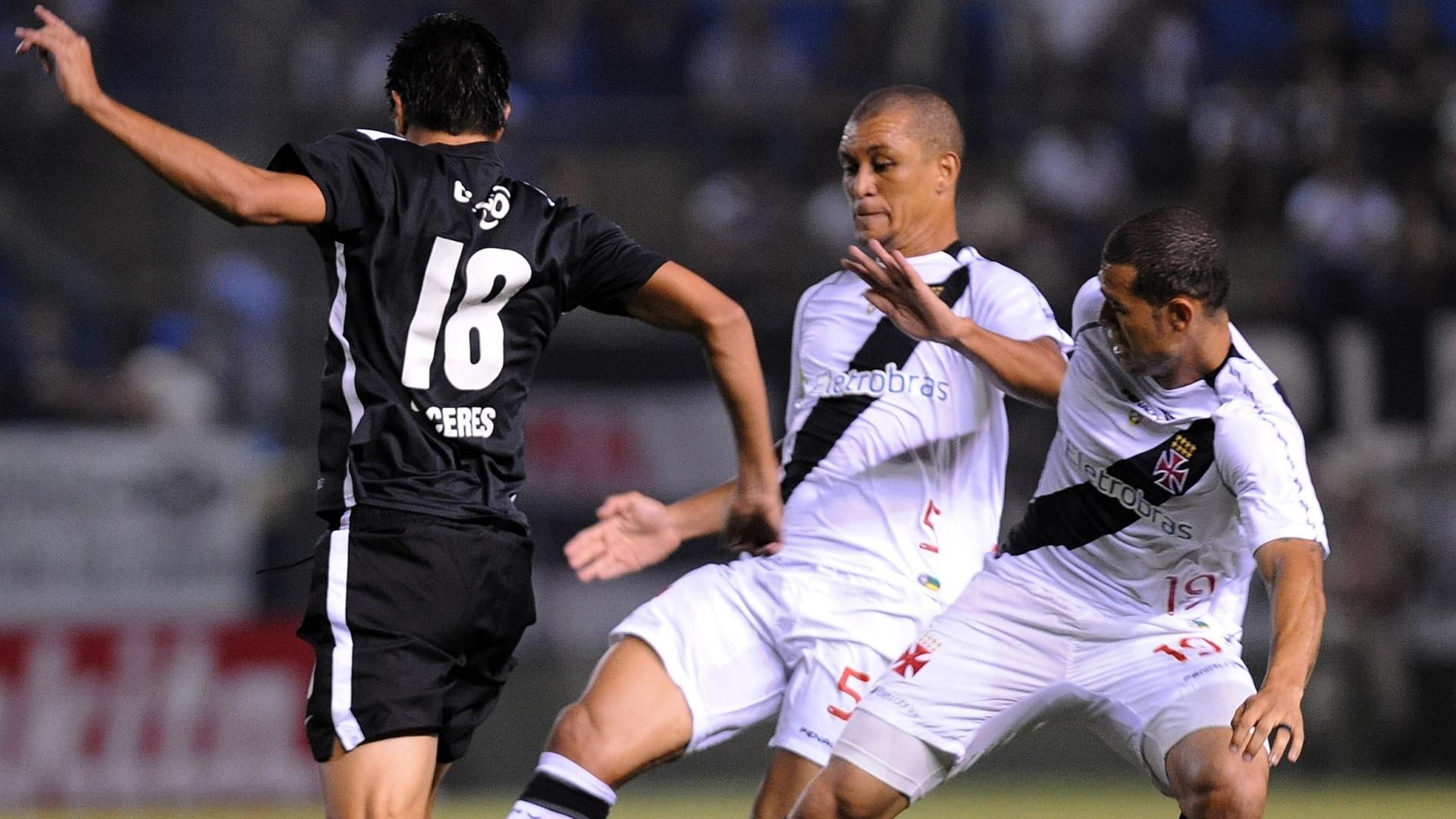 Eduardo Costa e Nilton, do Vasco, tentam roubar a bola do jogador do Libertad