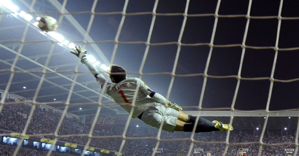 Goleiro do Atlético de Bilbao salta para tentar defender o chute de Wayne Rooney