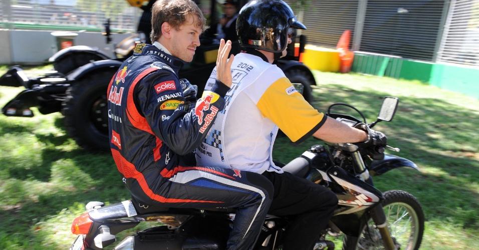 Sebastian Vettel pega uma carona para voltar aos boxes do circuito de Albert Park