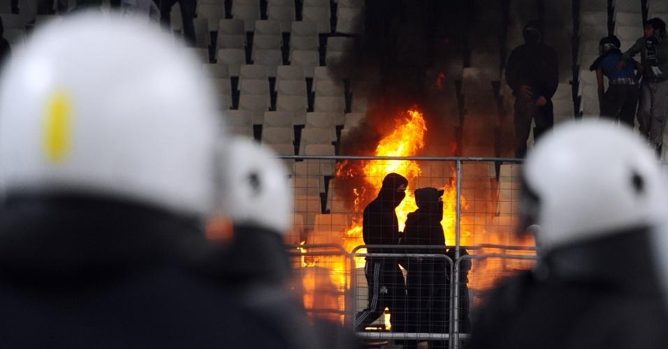 Policiais observam as chamas nas arquibancadas do estádio grego