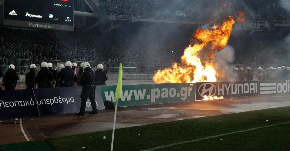 Policiais observam chamas no estádio durante partida do campeonato grego de futebol