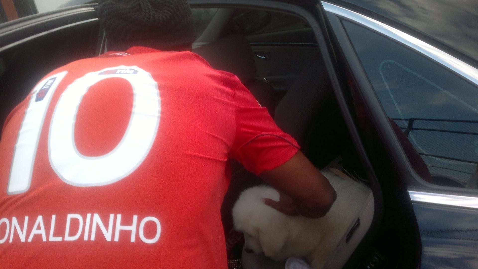 Ronaldinho acomodou o cachorro no banco de trás de seu carro antes de deixar a Gávea