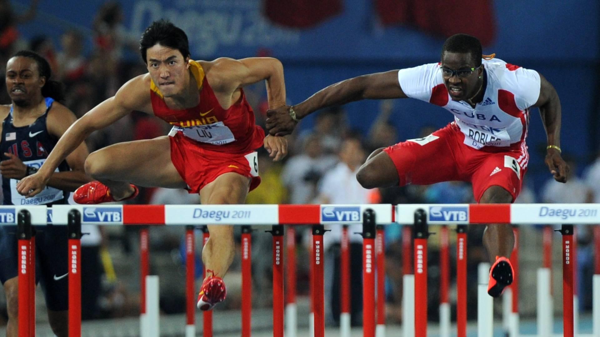 Dayron Robles toca o braço esquerdo do chinês Liu Xiang durante a disputa da final dos 110 m com barreiras no Mundial de Daegu (29/08/2011)