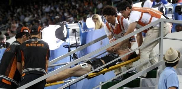 Neozelandês Nicholas Willis deixa o estádio em Daegu carregado após cair com um esbarrão na semifinal dos 1.500m masculino (01/09/2011)