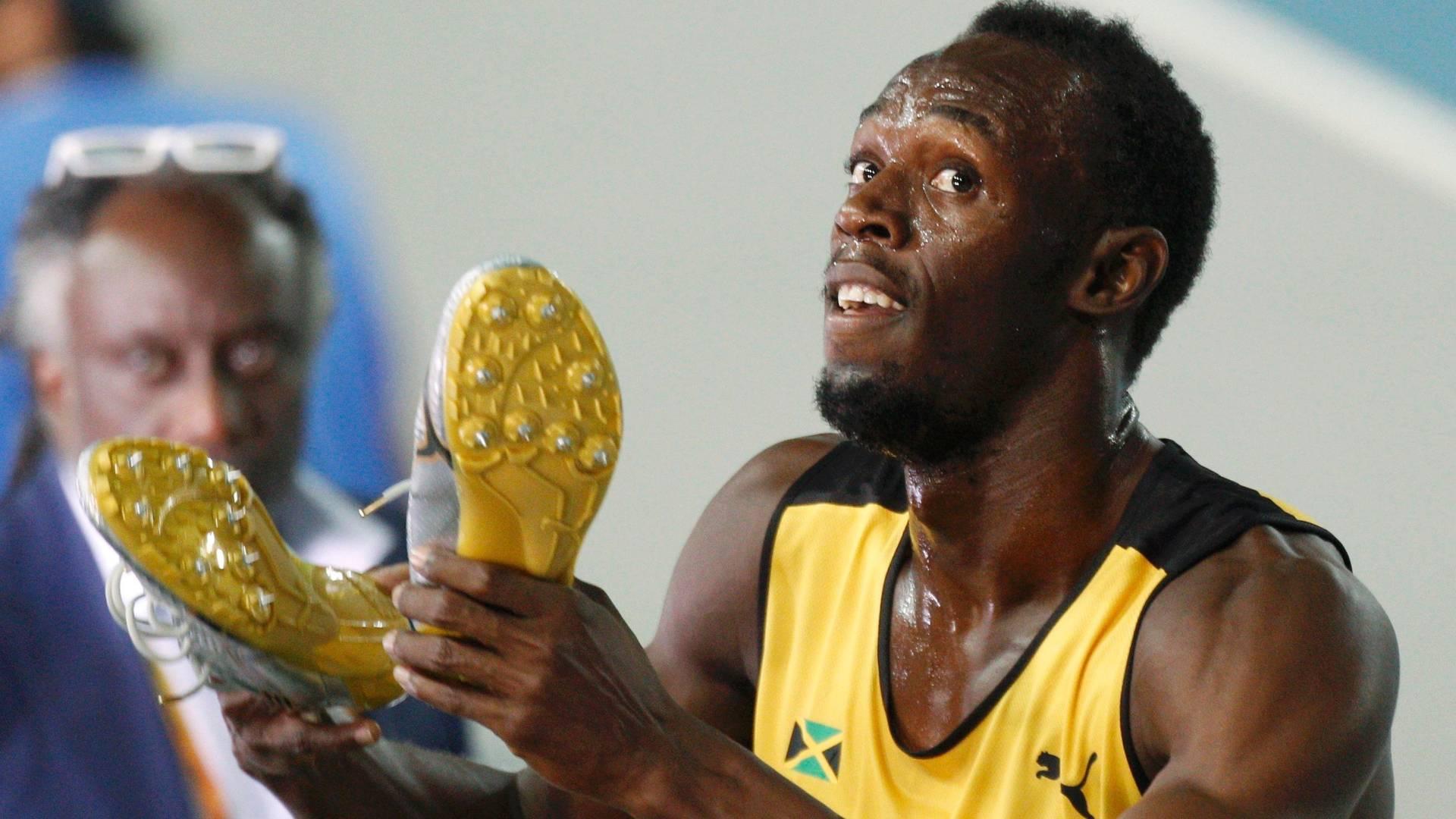 Usain Bolt exibe suas sapatilhas fazendo piada após a semifinal dos 200m em Daegu (02/09/2011)