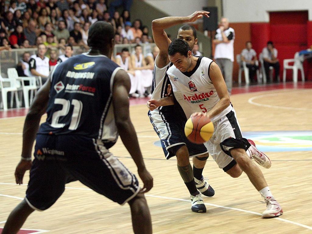 Manteguinha tenta passar pela marcação durante o duelo entre Joinville e Minas (20/04/11)