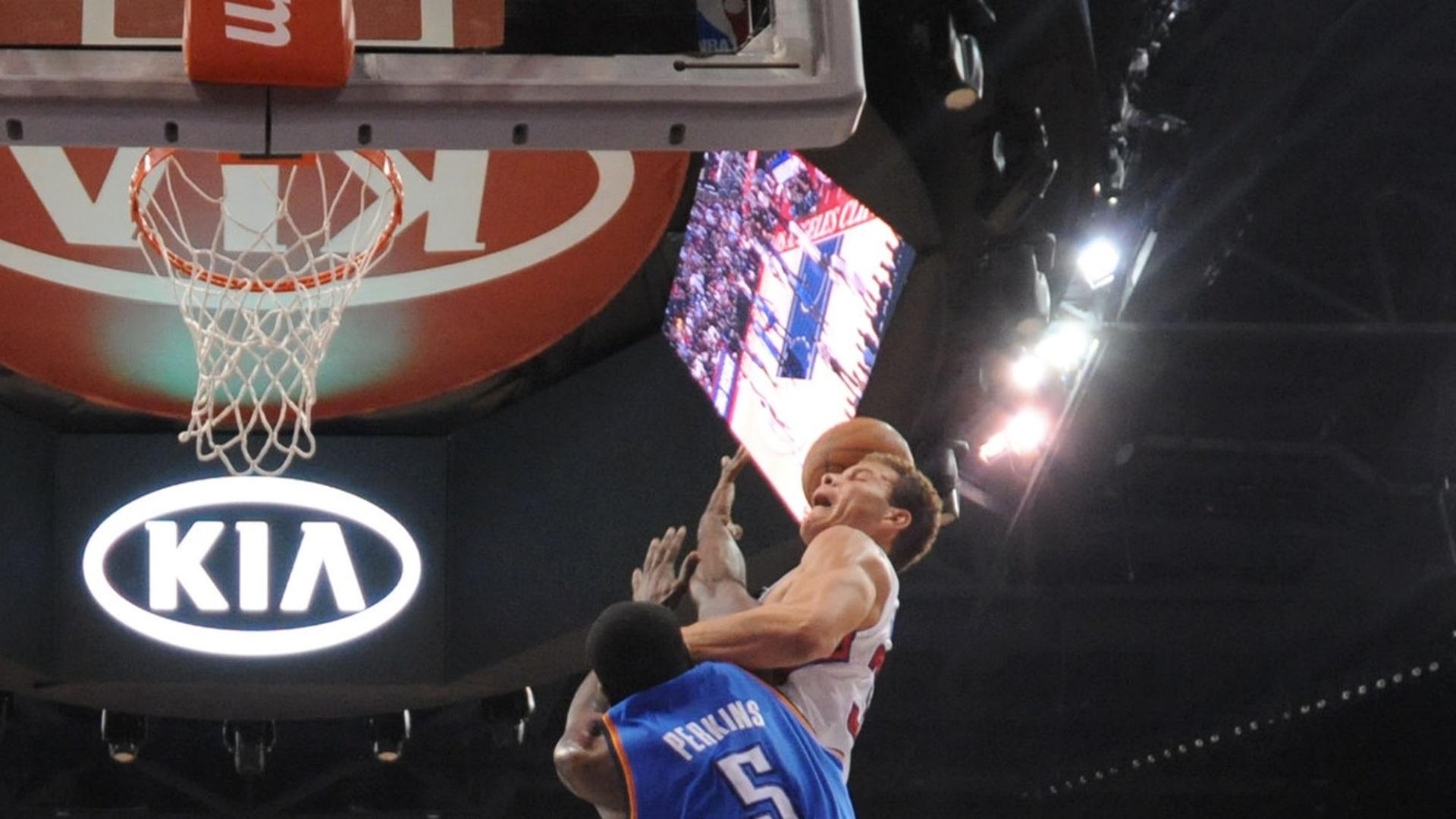 Blake Griffin, Los Angeles Clippers, acertou a cesta com uma mão só após saltar sobre o corpo de Kendrick Perkins, do Oklahoma City Thunder, em partida pela NBA
