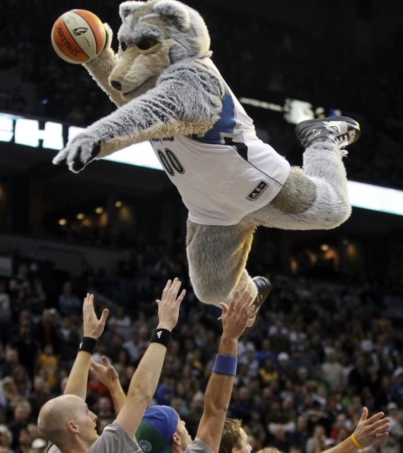 Crunch, mascote do Minnesota Timberwolves, voa sobre grupo de pessoas para enterrar durante intervalo de jogo