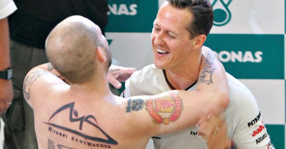 Torcedor com tatuagens em homenagem ao piloto abraça Michael Schumacher