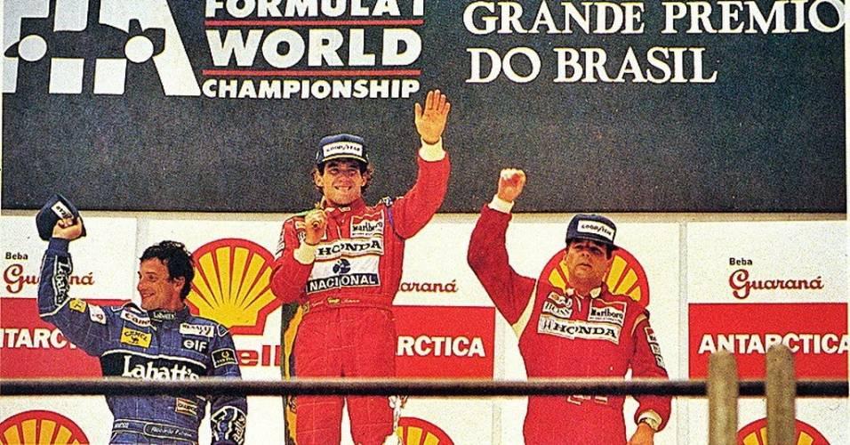 Ayrton Senna acena no pódio do GP do Brasil de 1991 ao lado de Riccardo Patrese (e) e Gerhard Berger