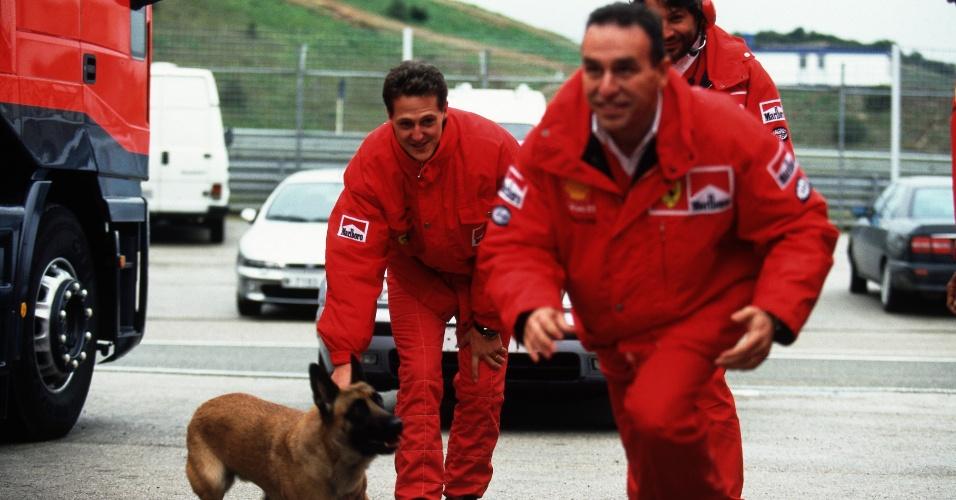 Schumacher e mecânico da Ferrari brincam com cachorro em Jerez, em 1997