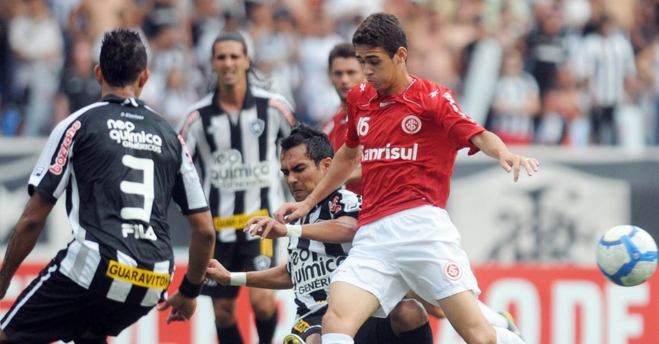Meia Oscar, do Internacional, tenta passar pela marcação do Botafogo, no Engenhão