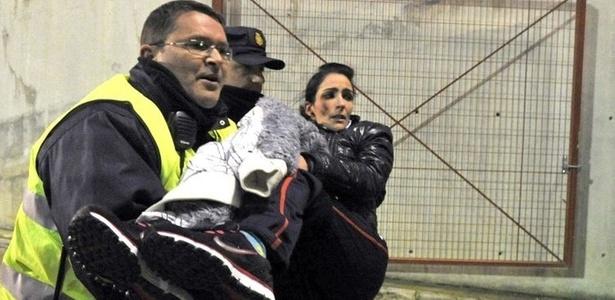 Policiais ajudam torcedora a sair do estádio Los Cármenes depois do tumulto que tomou conta da arquibancada quando a torcida do Granada comemorou um gol sobre o Huelva. Alguns ficaram feridos