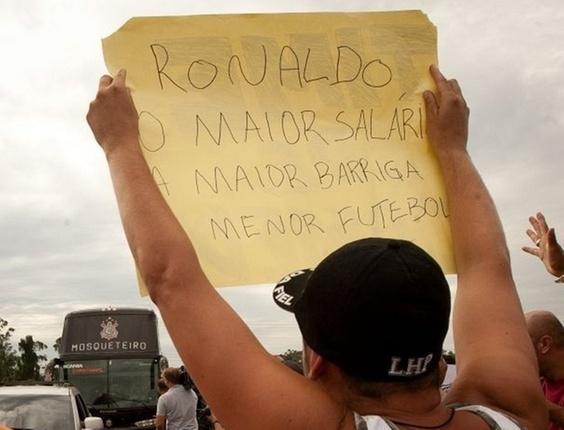 Torcedor do Corinthians segura cartaz com crítica a Ronaldo em protesto no CT Joaquim Grava