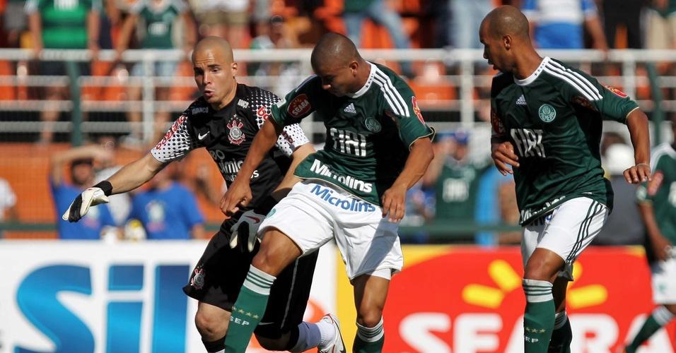 Observado por Dinei (d) e pelo goleiro corintiano Julio Cesar (e), Maurício Ramos tenta um chute a gol para o Palmeiras