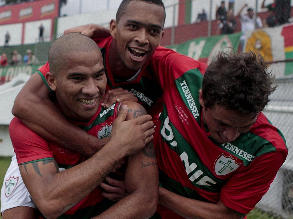 Jael (esq) é abraçado após marcar um gol de pênalti para a Portuguesa