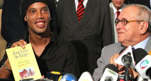 Ronaldinho exibe livro de José Lins do Rego em evento da Academia Brasileira de Letras. A entidade homenageou o Flamengo na comemoração dos 110 anos de nascimento do autor rubro-negro