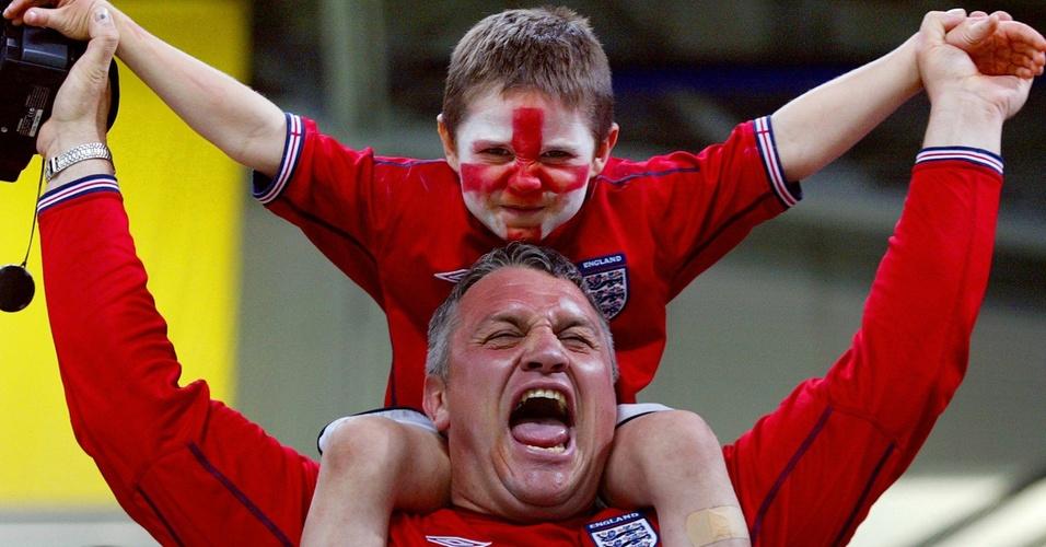 Na Copa de 2002, torcedor inglês vibra com a vitória sobre a Argentina, levantando um menino com a bandeira inglesa pintada no rosto