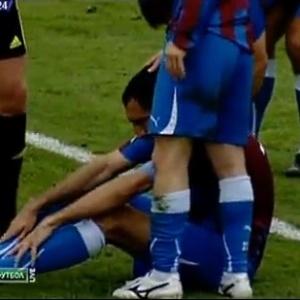 Jogador cai no chão após levar bolada na cabeça de Roberto Carlos