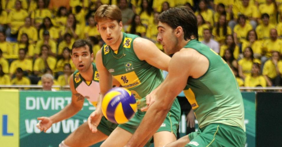 Observado por Murilo, Giba tenta o passe em partida pela seleção brasileira