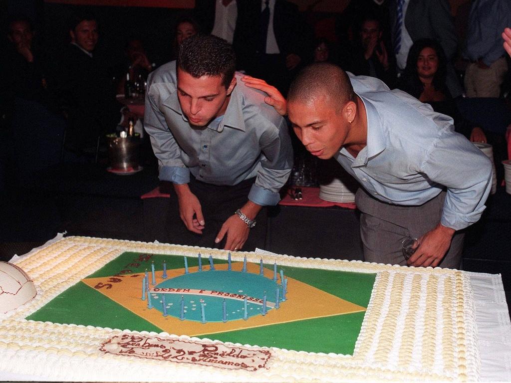 os jogadores brasileiros Ronaldinho e Zé Elias, da Internazionale, sopram velas do bolo de aniversário durante festa realizada em boate milanesa