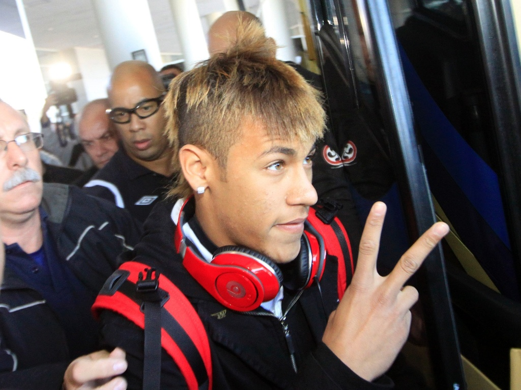 Com cabelo mais loiro do que o normal, Neymar acena ao desembarcar no Uruguai para final da Libertadores (14/06/2011)