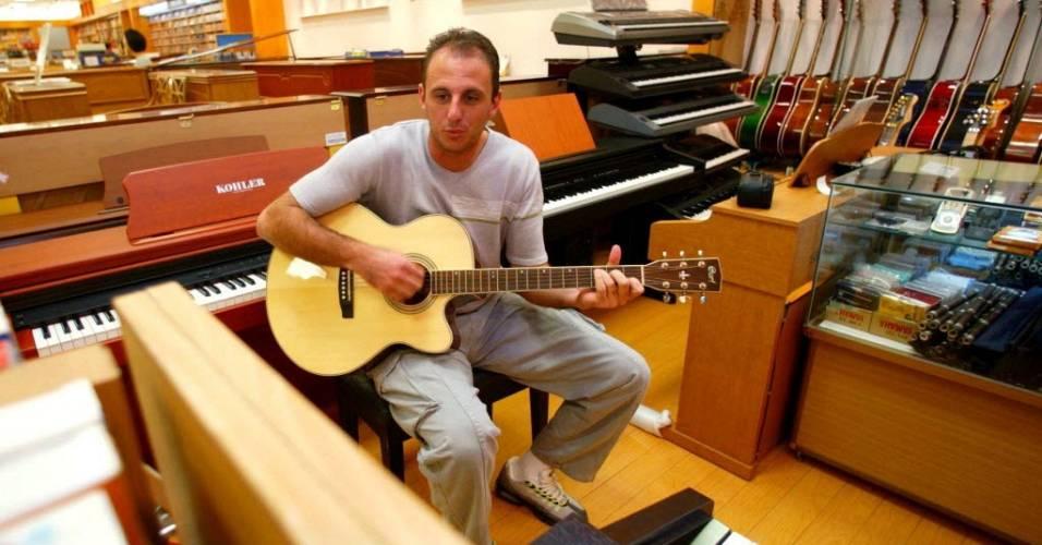 Rogério Ceni toca violão em uma loja de instrumentos em São Paulo