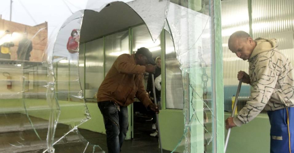 Funcionários limpam estragos causados por confusão entre jogadores e torcedores no Santo André (21/08/2011)
