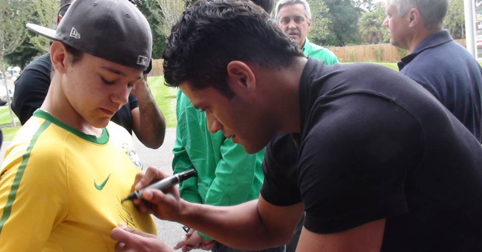 Hulk autografa camisa de torcedor brasileiro na porta de hotel em Londres